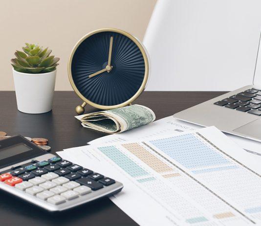 Em cima de uma mesa está um laptop, um relógio, um bolo de dinheiro, moedas, um pequeno vaso, calculadora e folhas impressas com tabelas coloridas. Parece se tratar de um ambiente doméstico em que a pessoa usa para trabalhar. A ideia é mostrar que o empresário não deve misturar as contas da pessoa física com a jurídica. O melhor a se fazer é cuidar do controle financeiro.