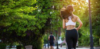 Jovem mulher está correndo numa pista de cooper para manter a saúde. É um dos exercícios físicos bem fáceis.