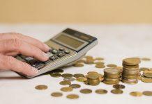 Calculadora sendo usada por um homem. Ao lado dela, há várias moedas espalhadas pela mesa. A ideia é mostrar que o momento atual é de fazer as contas para aproveitar as oportunidades de negócios a partir da nova taxa de juros.