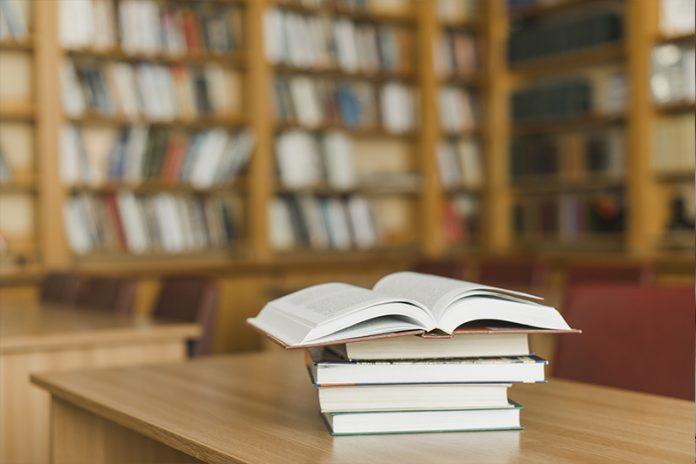 Foto de uma biblioteca, mostrando ao fundo uma estante repleta de livros. Mais à frente, aparece uma mesa de madeira, onde estão empilhados quatro livros fechados e em cima deles, um aberto.
