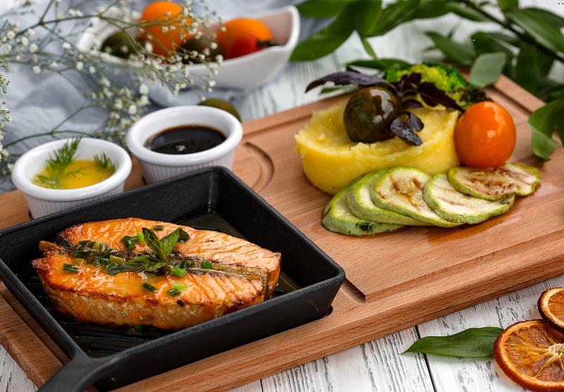 Imagem de uma mesa servida com uma refeição bastante saudável. No prato à esquerda há um salmão assado; no prato ao lado existem alguns legumes.