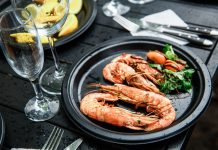 Imagem de um prato com camarão fresco, tendo legumes como acompanhamento.