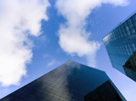 Dois imponentes e sofisticados prédios com fachada de vidro se mantêm lado a lado, como se estivessem conversando lá nas alturas, com o topo tão perto do céu. A ideia é fazer uma analogia com os poderosos bancos, que se entendem entre eles, longe do que acontece na rua com as pessoas. Os bancos praticam elevada taxa de juros.