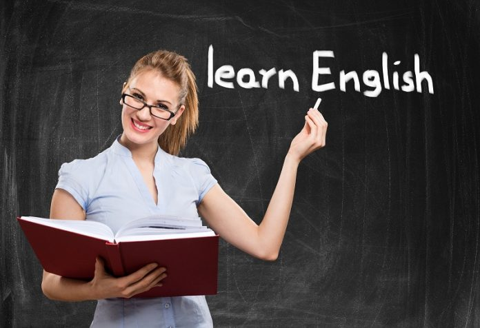 Uma jovem mulher, loira e de óculos, está na frente de uma lousa. Lá está escrito aprenda inglês e, segurando um giz, ela aponta para essa frase. Seu objetivo é ensinar a falar inglês.
