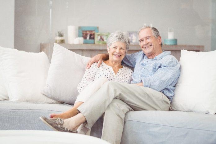 Casal de idosos que trabalham com marketing de rede estão sentados confortavelmente no sofá de uma casa elegante.