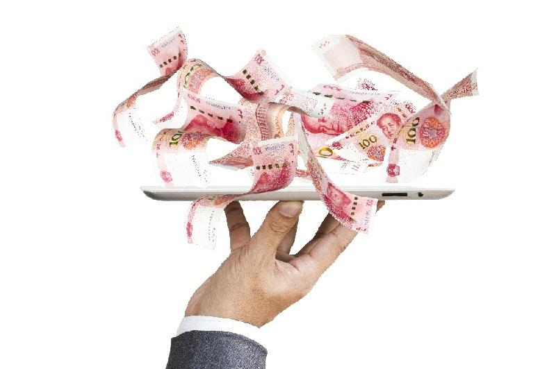 A mão de um homem segurando um celular, de onde saem várias notas do dinheiro chinês. O celular tem aplicativo para uso do QR code.