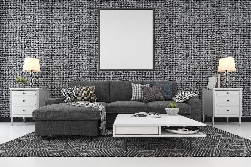 Sala elegante, com sofá e parede cinzas, tem um quadro em branco pendurado na parede.