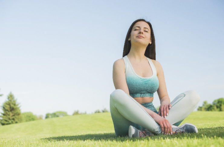 Mulher sentada de pernas cruzadas num parque, reflete após fazer exercícios e isso é bom para a saúde.