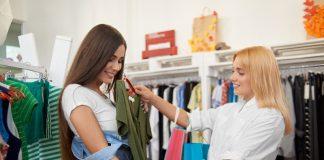 Moça compra roupas no comércio local existente no seu bairro.