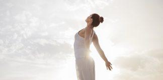 Mulher está no topo da montanha, em pé e de braços abertos, contemplando um dia de sol. Thetahealing a ajudou.