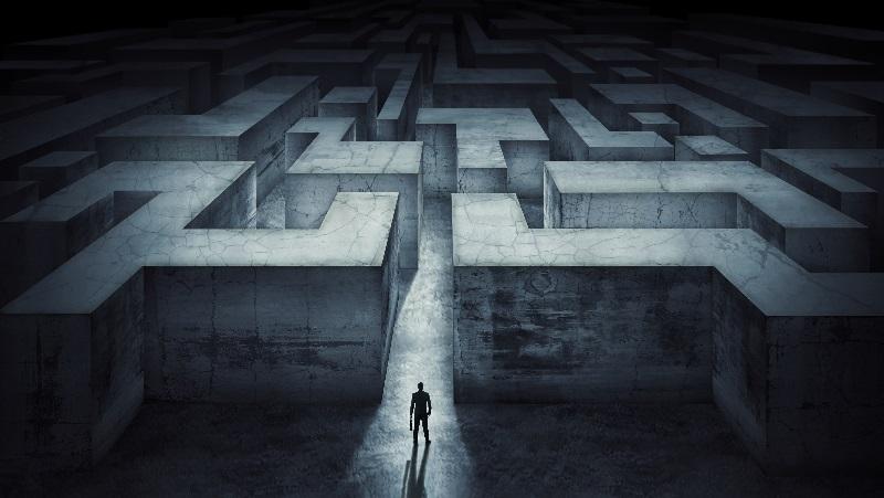 Homem está na entrada de um labirinto, que representa suas dúvidas e a Constelação Familiar pode ajudar nesse sentido.