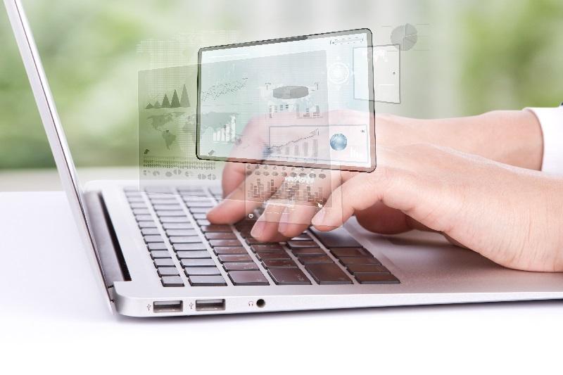 Homem digita um laptop para atualizar o seu blog.