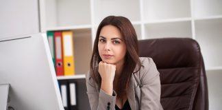 Mulher executiva está em sua mesa de trabalho e olha um blog.