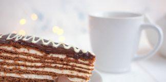 Uma deliciosa fatia de bolo é servida acompanhada de dois corações de chocolate. Uma xícara branca aparece ao fundo.