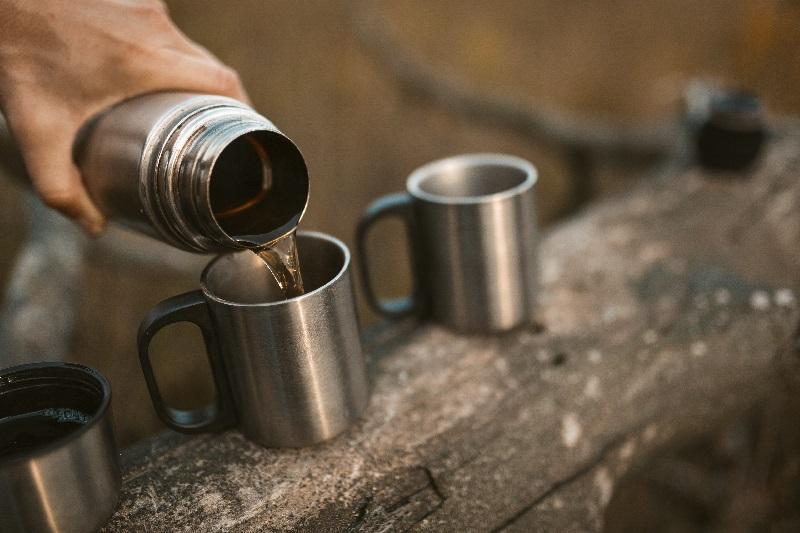 Homem usa garrafa térmica para servir chá.