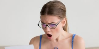 Mulher espantada olha carta em que é informada de que está inadimplente.