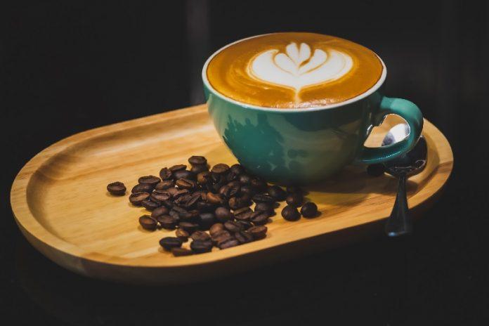 Xícara de café, com um coração espmado, servida numa bandeja de madeira.