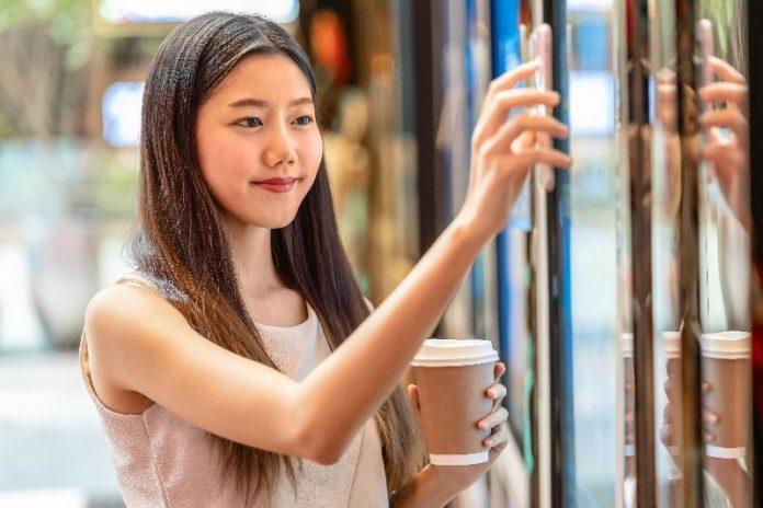 Asiática aponta o celular para uma máquina com alimentos e vai fazer pagamento por aproximação.