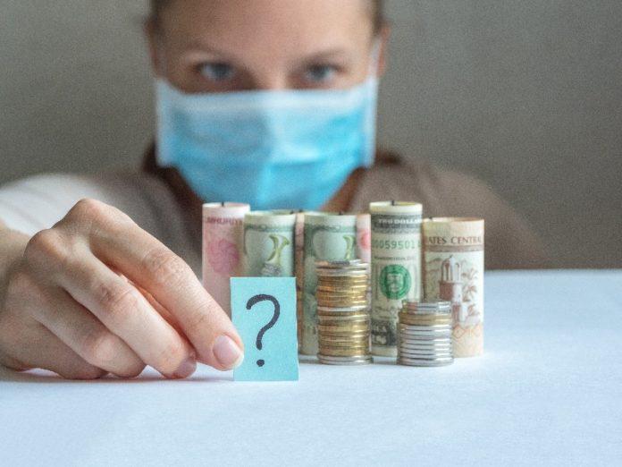 Mulher olha para rolos de dinheiro e segura um ponto de interrogação porque não sabe a saída para a crise econômica.