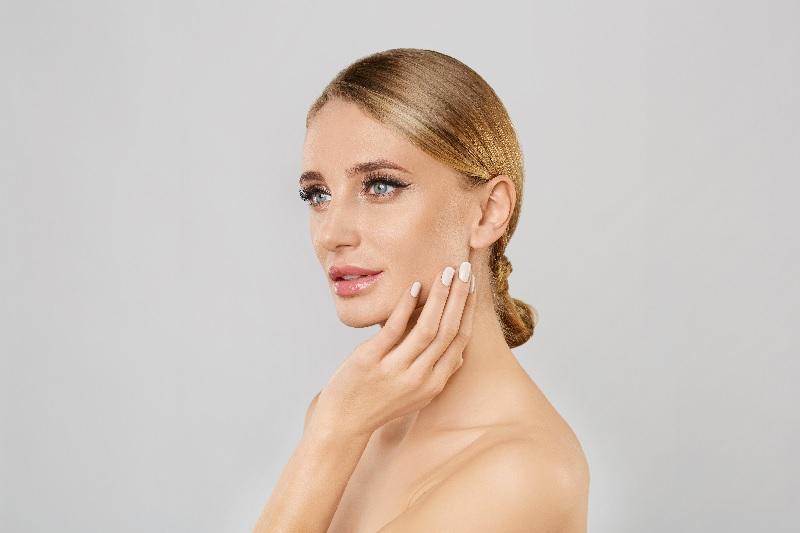Mulher toca o rosto para sentir o resultado do Facelift.
