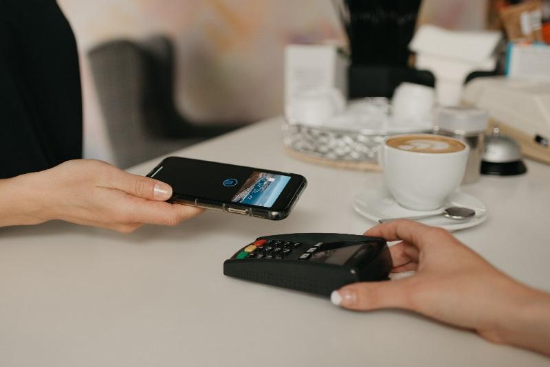 Moça aponta seu celular para a maquininha de débito e faz o pagamento do seu café.