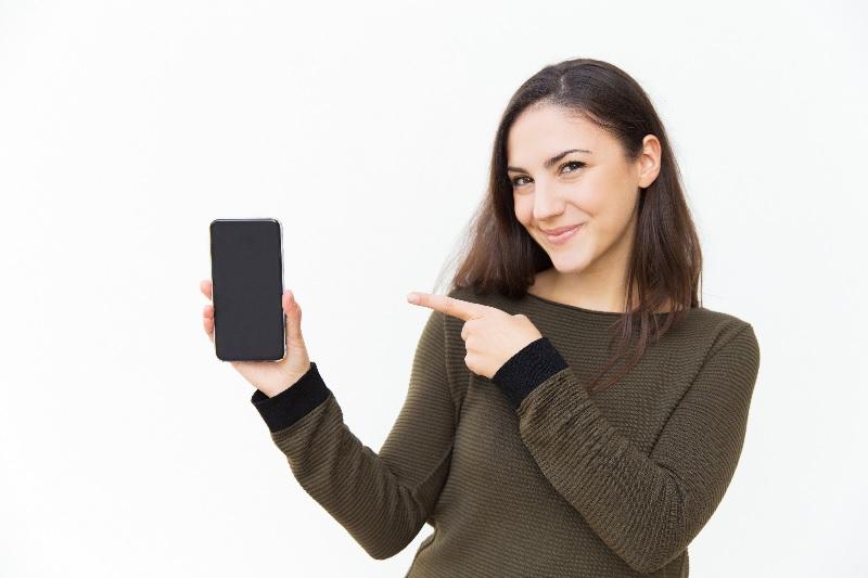Mulher mostra smartphone e usa aplicativo beone.