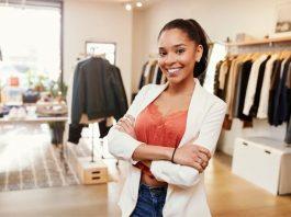 Empresária está em sua loja de roupas, preparada para atender na Black Friday.