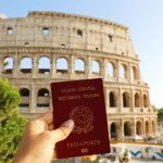 Mulher segura passaporte de cidadania italiana, em frente ao Coliseu.em