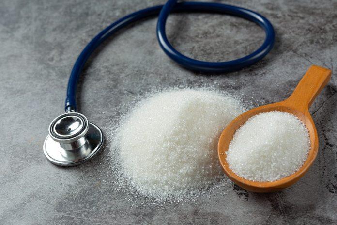 Estetoscópio está ao lado de um punhado de açúcar e chama a atenção ao perigo do diabetes.