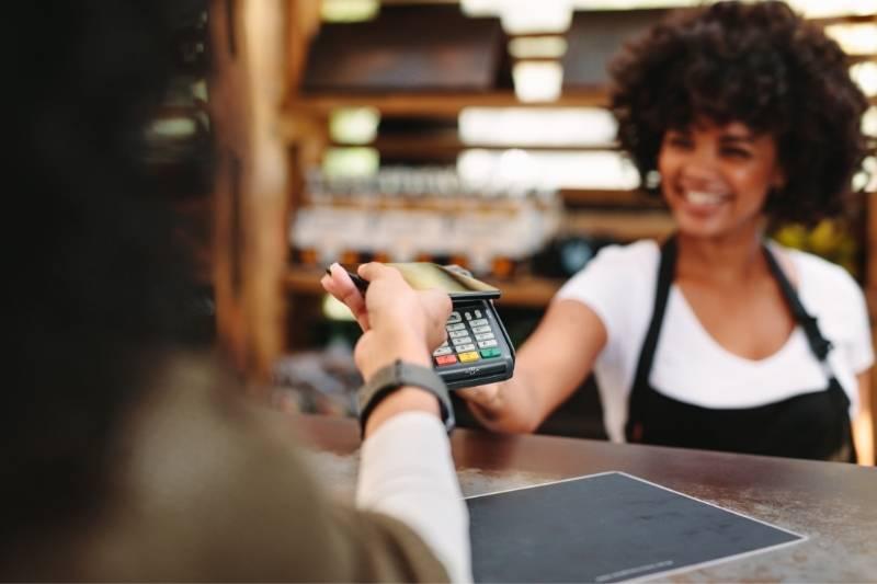 Mulher paga a conta usando o celular e aplicativo do beOne, seu banco virtual.