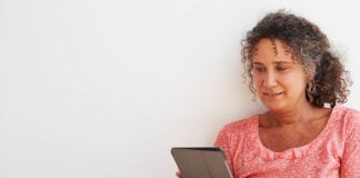 Mulher sentada mexe no tablet para consultar o banco virtual beOne.