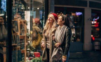 Duas mulheres olham uma vitrine bem montada para as vendas de Natal.