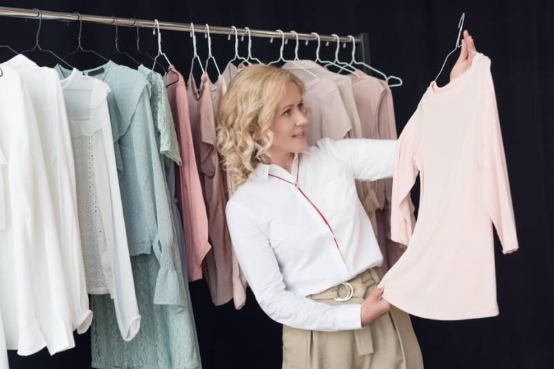 Mulher escolhe roupa durante as compras de Natal.