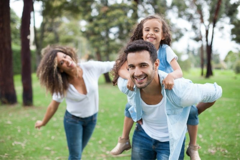 Casal com filha de 7 anos brinca no parque e está feliz porque não se preocupa com o convênio.