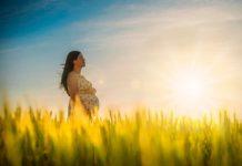 Mulher está contemplando a na natureza e curtindo a gravidez saudável.