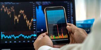 Cliente olha o celular, para ver a movimentação financeira por meio do Open Banking.